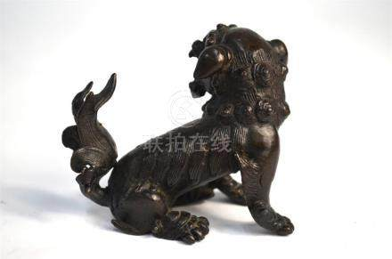 A small, Chinese bronze figure of a Buddhist lion, looking to the left; 7.5 cm high, Qing