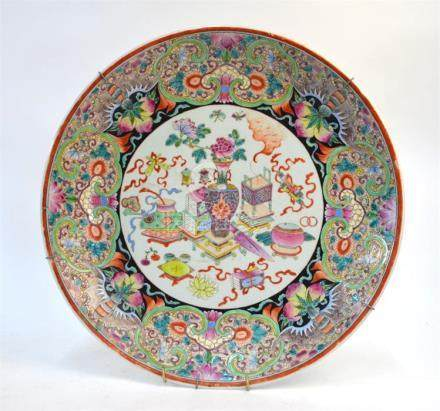 A famille rose circular dish, decorated with a central design of scholars implements and sacred