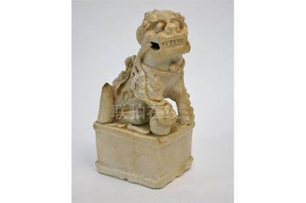 A Blanc-de-Chine figure of a male Buddhistic Lion with his right paw on a ball; probably a joss-