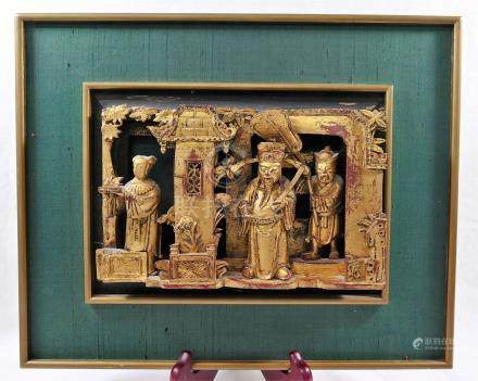 A framed Chinese carved gilt wood panel, of three figures within an interior, 16.5cm x 23.