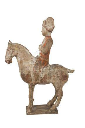 A Chinese pottery figure of a horse and rider, Tang dynasty, with traces of painted decoration to