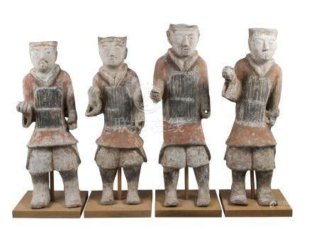 Four large Chinese grey stoneware guardian figures, Han dynasty, each modelled standing, wearing a