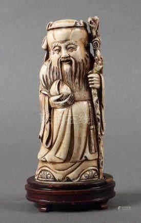 GelehrterChina, um 1900, stehender Gelehrter mit langem Bart, in der linken Hand einen Wurzels