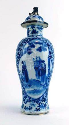 A late 19th century Chinese blue and white covered vase of baluster form decorated with two panels