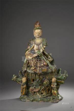 Le Boddhisattva Kwan Yin assis en délassement sur un haut tertre moulé à la base [...]