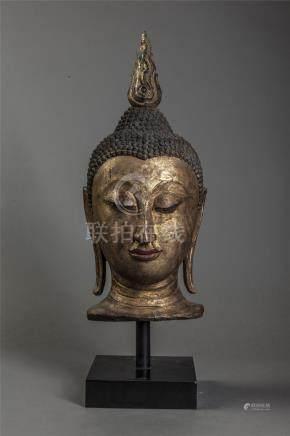 Tête de Buddha coiffée de fines bouclettes surmontée d'un haut rasmi. Bois laqué [...]