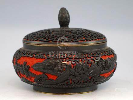 Chinese cinnabar lacquered red and black jar and cover decorated with scrolling foliage and