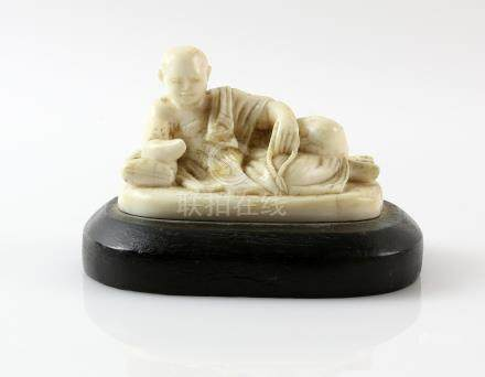 Early 20th century Chinese carved ivory figure of a man reclining, on wooden base, figure 6.5cm