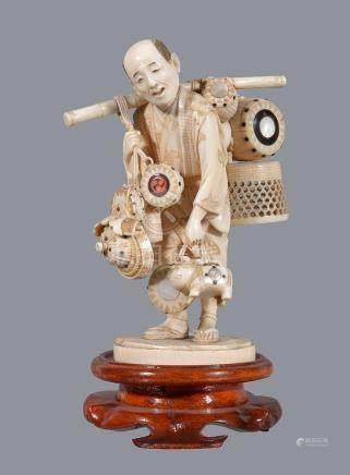 ϒ A Japanese Ivory Okimono of a Toy Seller