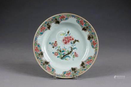 Assiette. A décor d'asters et de pivoines en fleurs. Aile à motifs découpés. Porcelaine de C