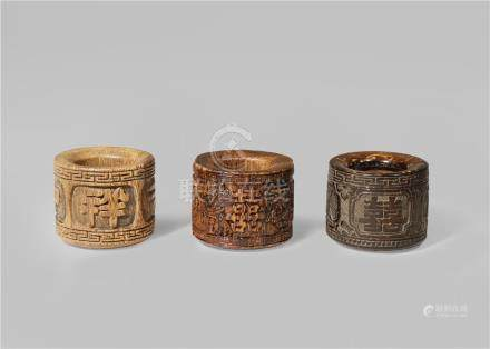 TWO CHINESE ALOESWOOD AND ONE CARVED COCONUT ARCHER'S RINGS QING DYNASTY One carved with shuangxi