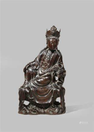 A CHINESE ZITAN FIGURE OF GUANYIN REPUBLIC PERIOD Seated on a rock pedestal in a relaxed pose,