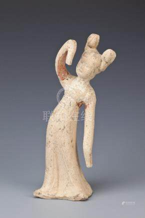 A CHINESE POTTERY MODEL OF A DANCER TANG DYNASTY Standing, wearing a long robe with elongated