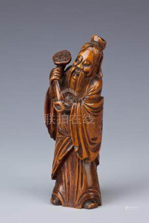 A CHINESE BOX WOOD CARVING OF AN IMMORTAL QING DYNASTY Standing, wearing long robes, smiling, with