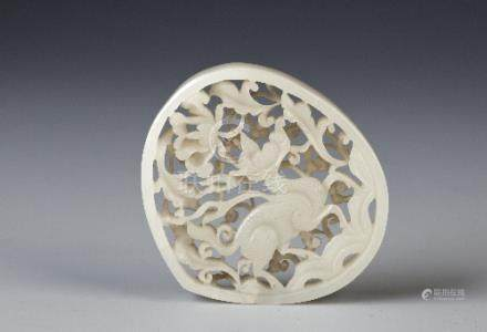 A CHINESE WHITE JADE RETICULATED PLAQUE QING DYNASTY The peach-shaped body carved with a qilin