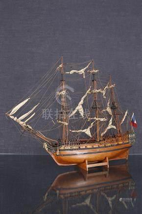 Maquette d'un trois-mâts  En bois sculpté et laqué, cordage et tissu Sur son support en bois