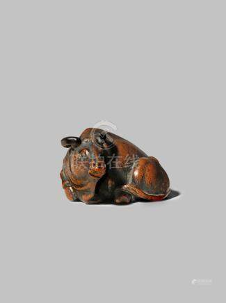 A JAPANESE WOOD NETSUKE EDO/MEIJI PERIOD Depicting a large ox reclining, its legs neatly tucked