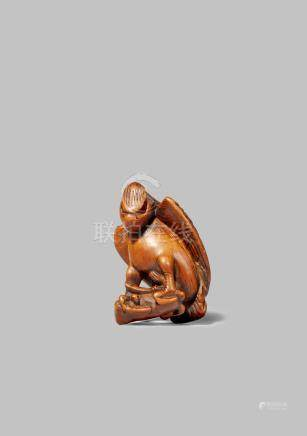 A JAPANESE WOOD NETSUKE EDO 1603-1868 Depicting a fierce-looking eagle restraining a small fox