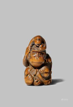 A JAPANESE WOOD NETSUKE EDO 1603-1868 Depicting a large monkey seated with her two young, tenderly