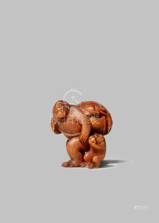 A JAPANESE WOOD NETSUKE MEIJI 1868-1912 Depicting a monkey with its young and carrying a giant peach