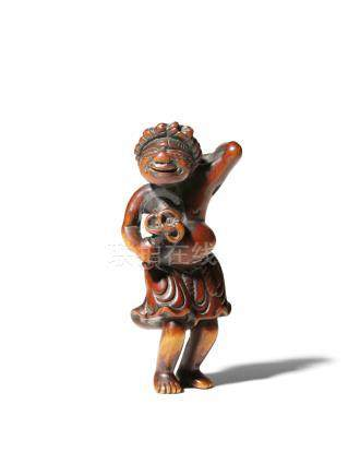 A JAPANESE WOOD NETSUKE EDO 1603-1868 Depicting a standing South Sea Islander, holding a shakujo