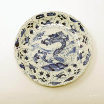An early Chinese Kangxi period blue and white plate, central dragon design within nautical border,
