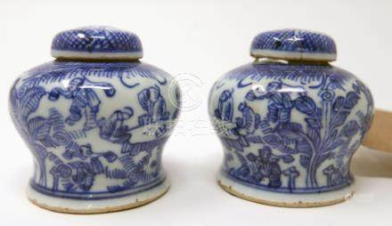 A pair of 18th century Chinese blue and white miniature temple jar and covers, festive figural