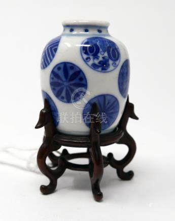An 18th century Chinese blue and white miniature vase, circle design, on hardwood stand, H.5cm