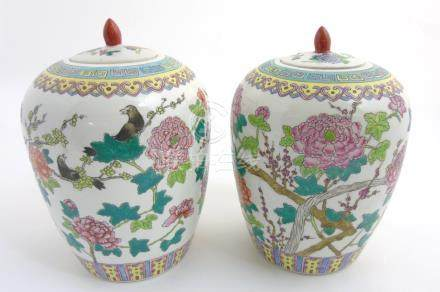 A pair of Famille Rose lidded vases / ginger jars of ovoid form,