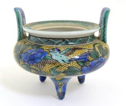 A Chinese three legged, two handled censer, decorated with a bird and flowers.