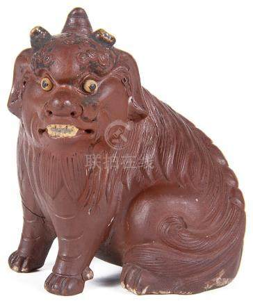 A Japanese pottery figure 19th/early 20th century Modelled as a seated horned komainu lion dog with