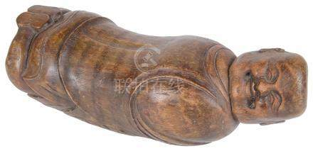 A Chinese carved bamboo pillow 19th century In the shape of a reclining Bodai lying on his belly