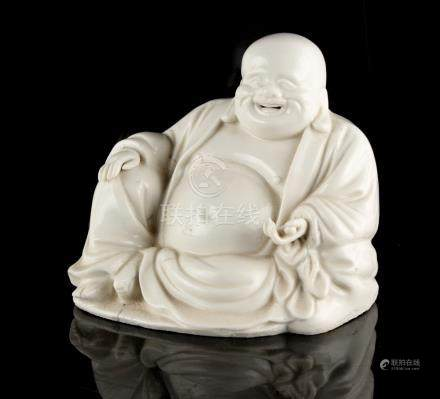 A Chinese blanc de Chine figure of Buddha or Budai, 18th century, modelled seated, 5.45ins. (13.