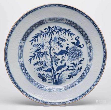Gr. rd. Platte, China 20. Jh.Blaumalerei. Spiegel m. Bambus- u. Päoniendekor, reliefierte Fahne m.