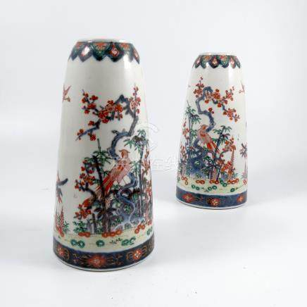 A pair of Japanese vases, decorated in the Imari palette with birds and flowers in a landscape,