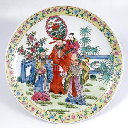 An Oriental wall plate, decorated with figures in a landscape to a yellow ground border, diameter