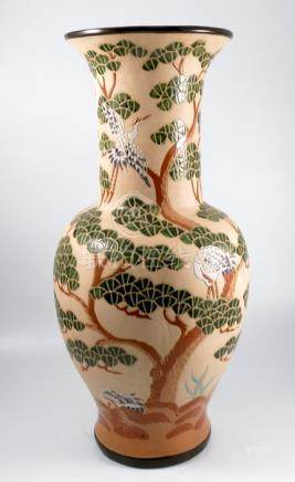An oriental design pottery vase, of baluster form, decorated with cranes and foliage to a beige