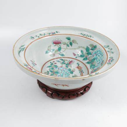A Chinese famille rose bowl, decorated with flowers and insects, diameter 11.5ins, on a wooden