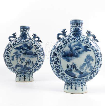 A pair of Chinese blue and white pilgrim vases, decorated with a panel of figures in a landscape,