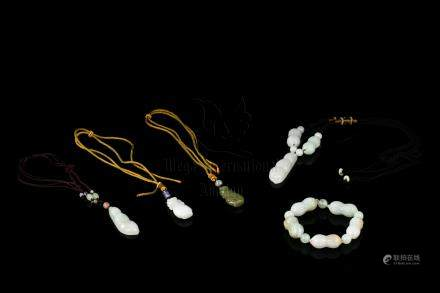 FOUR JADEITE CARVED PENDANTS AND A JADEITE CARVED BRACELET