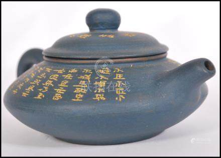 A Chinese Yi Xing teapot having a blue pottery ground with gilt Buddhist Scriptures and