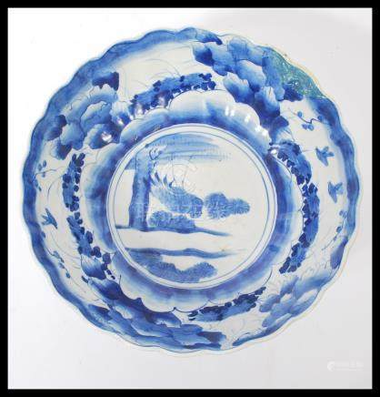 A 19th century Chinese blue and white bowl of scalloped form having hand painted decoration of birds