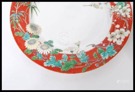 A pair of 19th century Chinese porcelain plates having a red ground with decoration of blossoming