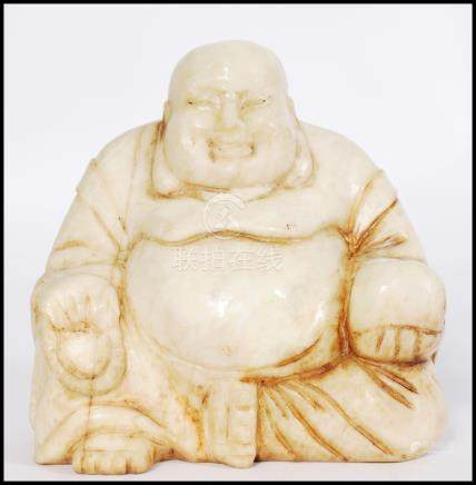 An early 20th century Chinese soapstone carving of a Chinese laughing Buddha carved in a seated