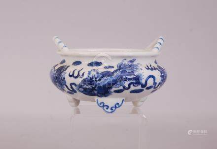 C19th Chinese blue and white tripod censer, painted with four lions at play, two loop handles rise