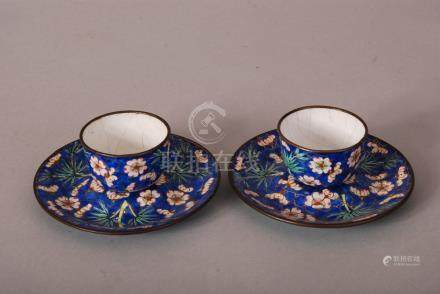 Pair of C18th/19th Chinese painted enamel cups and saucers, painted with bamboo and prunus in a blue