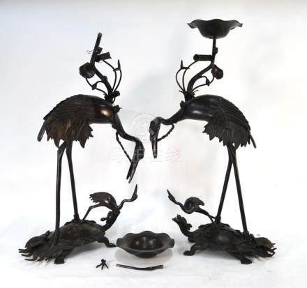 A pair of Japanese metal alloy figures of Manchurian tsuru; each bird standing on a minogame
