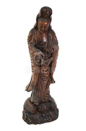 An Asian wood figure of the Bodhisattva, Guanyin or Sho Kannon, wearing a typical high chignon and