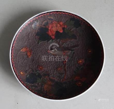 CHINEAssiette de forme ronde en porcelaine à décor intérieur en laque légèremen