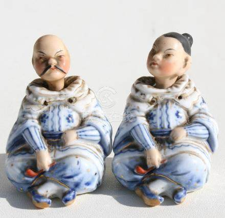 A pair of Victorian porcelain nodding figures in the form of a seated Chinese couple, 7cms (2.75ins)
